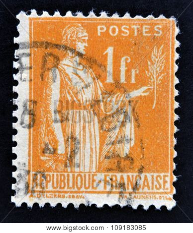 A stamp printed in France shows a woman with an Olive Branch in hand - allegory of Peace