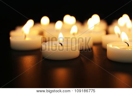 Alight candles in a row on black background, blurred