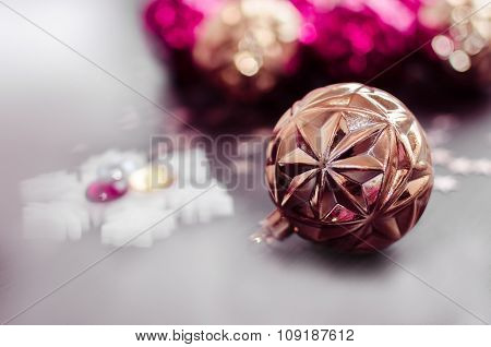 Gold Christmas Ball On Bokeh Background Of Xmas Ornaments.