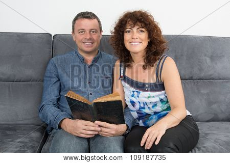 Happy Couple Reading Book And Laughing Having Fun On The Couch