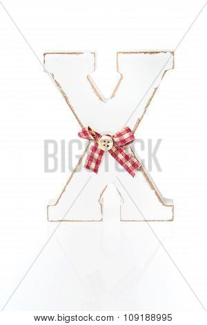 Wooden letter X decorated in Christmas spirit with ribbon and a button