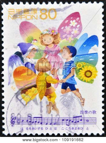 A stamp printed in Japan shows red headed fairy children representing the four seasons