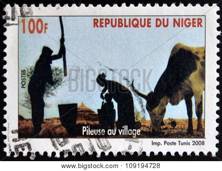 NIGER - CIRCA 2008: A stamp printed in Niger shows pileuse au village circa 2008