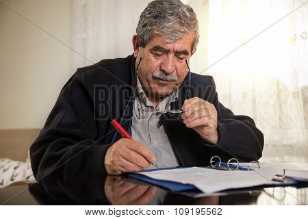 Senior Man Signing Papers