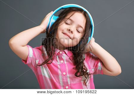 Beautiful little girl listen music with blue headphones on grey background