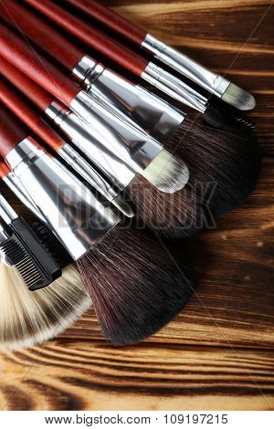 Makeup Brushes Set On A Brown Wooden Background