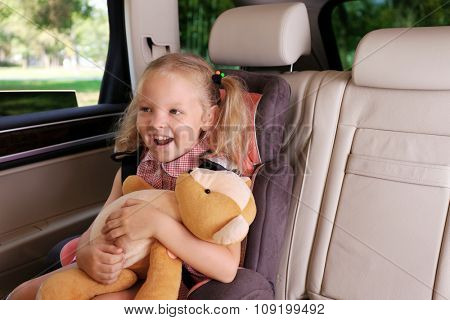 Beautiful happy girl with teddy bear sitting in the car