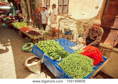 Old Man Sells Herbs, Beans And Pears On Rustic Street Market In Turkey