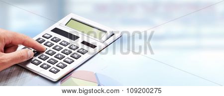 Hand with calculator over blue office background. Accounting.