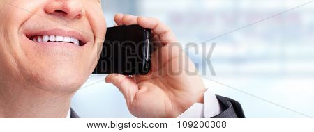 Hands of businessman calling by phone over blue background.