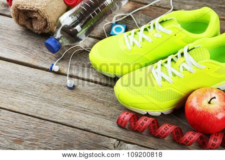 Shoe, Water, Tape Measure And Headphones On Grey Wooden Background