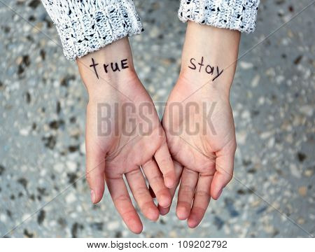 Hands of young woman with tattooed words on it, on ground background, close-up