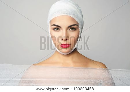 Young beautiful woman with a bandage on her head, holding gauze, on grey background