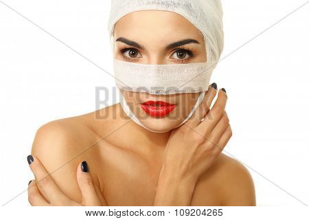 Young beautiful woman with a gauze bandage on her head and nose, isolated on white