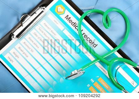Heart shaped stethoscope with medical record on blue uniform, close up