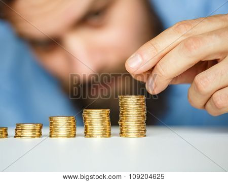 Business Man Stacking Gold Coins Into Increasing Columns