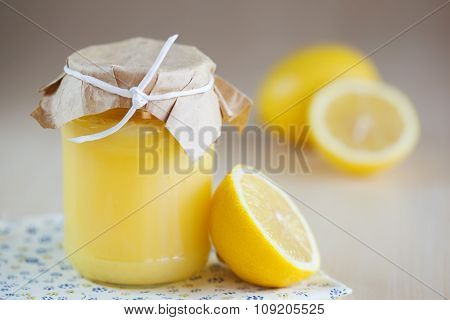 A homemade jar of lemon curd with a lemon and spoon