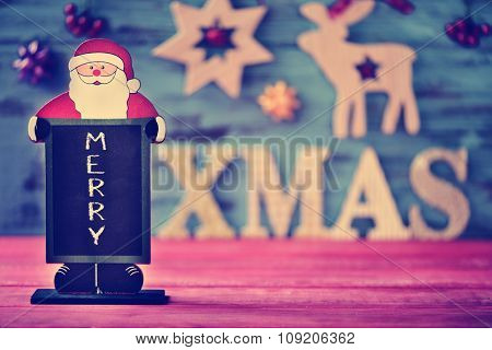 a chalkboard in the shape of santa claus with the text merry and wooden letters forming the text xmas on a blue rustic wooden surface with some different cozy christmas ornaments