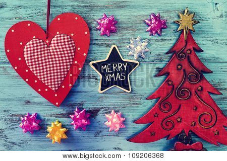 a star-shaped chalkboard with the text merry xmas written in it on a blue rustic wooden surface with a rustic wooden christmas tree and some other ornaments