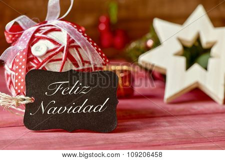 a black label with the text feliz navidad, merry christmas in spanish, and some different cozy christmas ornaments on a red rustic wooden surface