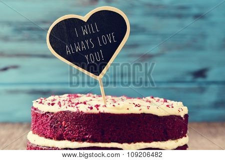 closeup of a red velvet cake topped with a heart-shaped chalkboard with the text I will always love you written in it, on a rustic wooden table