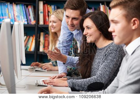 Tutor Helping Teenage Students Working At Computers