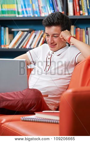 Male Teenage Student With Laptop Working In Library