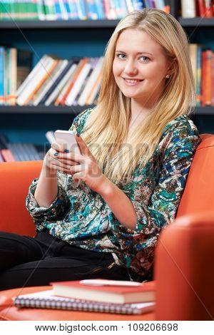 Female Teenage Student Using Mobile Phone In Library