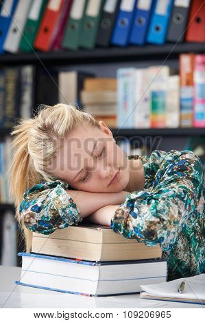 Tired Female Teenage Student Sleeping In Library