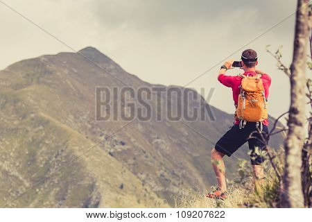Hiking man backpacker climber or trail runner in mountains looking at beautiful inspiring landscape