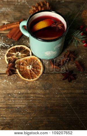 Decorated composition of mulled wine in mug on wooden table