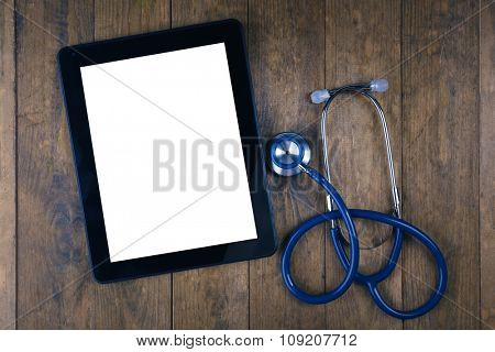 Blank tablet and stethoscope on wooden background