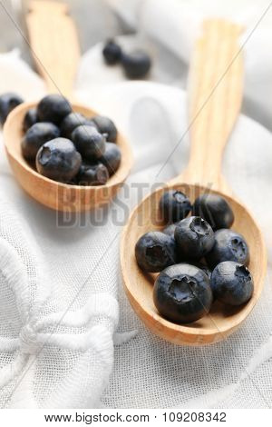 Fresh blueberries in spoons on table close up