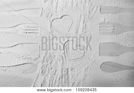 Flour sprinkled around kitchen utensils on light background