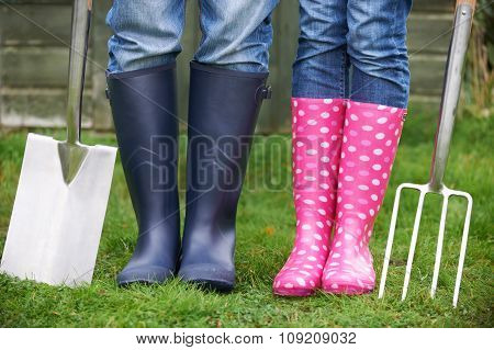 Close Up Of Couple Gardening Holding Spade And Fork