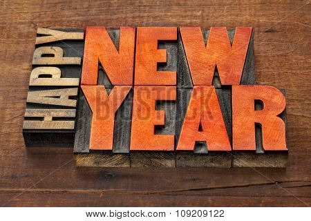 Happy New Year greeting card  - word abstract in vintage letterpress wood type blocks stained by red ink  on a grunge wooden background