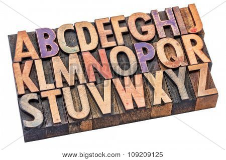 English alphabet in vintage letterpress wood type stained by color inks,  isolated on white