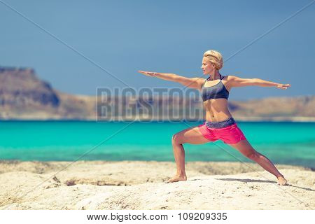 Yoga pose fit woman stretch and exercise on a beach and mountains. Girl doing yoga Virabhadrasana