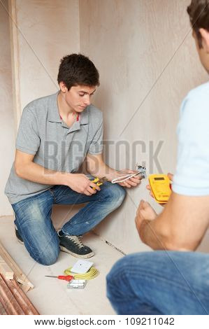 Electrician With Apprentice Working In New Home