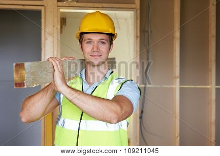 Builder Carrying Timber On Building Site