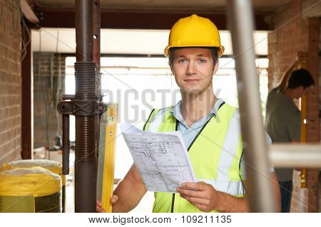 Portrait Of Builder On Site With Plans