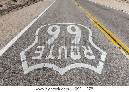 Upside down view of old Route 66 pavement sign in the Mojave desert.