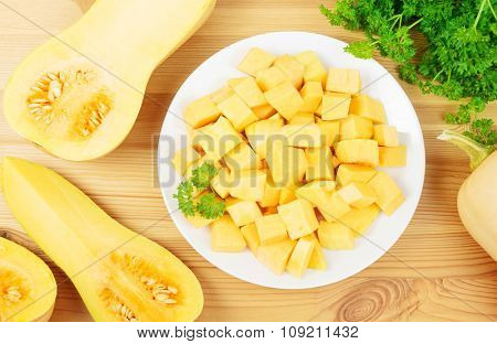 Plate with diced butternut squash and butternut squashes on a wooden background.