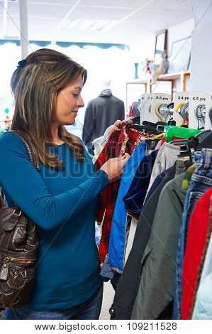 Woman Buying Children's Clothes In Charity Shop