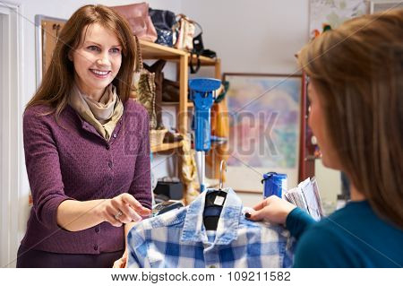 Woman Buying Shirt In Charity Shop