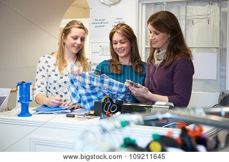 Three Female Volunteers Workers In Charity Shop