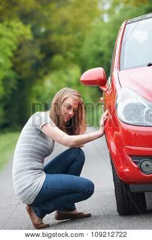 Female Motorist With Puncture On Country Road