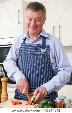Senior Man Enjoying Cooking In Kitchen