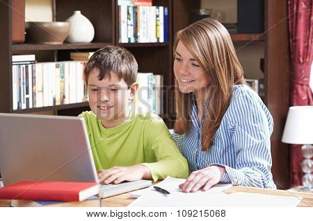 Tutor Helping Boy Studying At Home