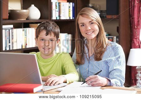 Female Tutor Helping Boy With Home Studies